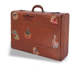 Brown suitcase with travel labels